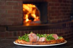 Pizza with roll of italian ham on burning oven Royalty Free Stock Photo
