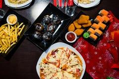 Pizza, rotoli, patate al forno ed un assortimento alimento sulla tavola Fotografie Stock