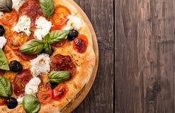Pizza rústica con el salami, la mozzarella, las aceitunas y la albahaca en de madera Foto de archivo