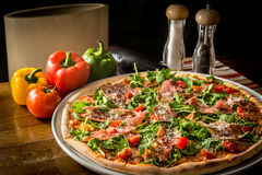 Pizza with rucola and Black Forest ham. On wooden table with vegetables and peppers royalty free stock image
