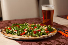 Pizza with rucola, cherry tomatoes and a glass of beer on a tebl Stock Photo
