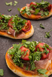 Pizza with rucola, tomato and ham in vertical format Stock Images