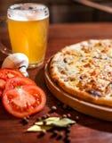 Pizza sabrosa con la cerveza en la tabla de madera foto de archivo