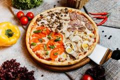 Pizza sabrosa deliciosa cortada con las verduras en la tabla de madera fotografía de archivo libre de regalías