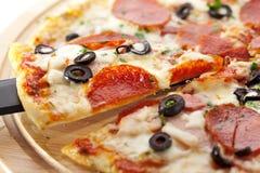 Pizza Salami. Pizza made with Salami, Mozzarella, Mushrooms, Olives and Tomato Sauce royalty free stock photo