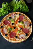 Pizza with salami, bacon, broccoli, olives on dard background. Royalty Free Stock Photos