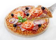 Pizza with salami, bacon, tomato and black olives. On white wooden table stock photography