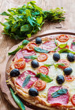 Pizza with salami, black olives and tomatoes. On the wooden table Royalty Free Stock Images