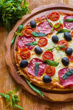 Pizza with salami, black olives and tomatoes. On the wooden table Royalty Free Stock Photo