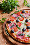 Pizza with salami, black olives and tomatoes. On the wooden table Stock Photos