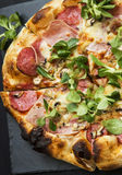 Pizza salami,cheese and ham with cornsalad leaves. Pizza salami and ham with cheese and cornsalad leaves , rustich fresh baked italian pizza stock photos