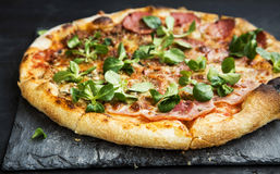 Pizza salami,cheese and ham with cornsalad leaves. Pizza salami and ham with cheese and cornsalad leaves , rustich fresh baked italian pizza stock photo