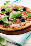 Pizza with salami, chili pepper and olives Stock Image
