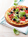 Pizza with salami, chili pepper and olives Stock Photos