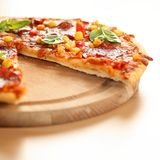 Pizza. With salami, corn and herbs on wooden tray royalty free stock image