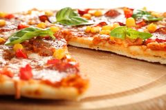 Pizza. With salami, corn and herbs on wooden tray stock image