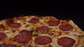 Pizza salami falls on a black surface stock footage