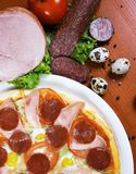 Pizza with salami, ham, edd and tomato Stock Images