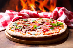 Pizza with salami, ham and vegetables Royalty Free Stock Images