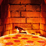 Pizza with salami and hot brick wall of oven. Italian pizza with salami and hot brick wall of wood burning oven stock photography