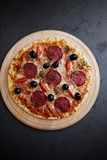 Pizza with salami, mozzarella cheese, cherry tomatoes, black olives and oregano. Home made food. Concept for a tasty and hearty me royalty free stock photo