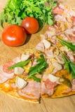 Pizza with salami, mozzarella, mushrooms, ruccola and tomatos Stock Photography