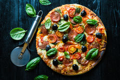 Pizza with salami,. Olives and basil stock photo