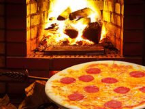 Pizza with salami and open fire in oven Stock Images