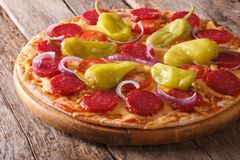 Pizza with salami, pepperoni peppers on table horizontal Royalty Free Stock Image
