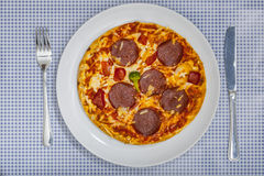Pizza Salami with silverware on blue checkered table cloth. Pizza Salami on white plate, with silverware on blue checkered table cloth Stock Image