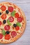Pizza with salami, tomato, cheese, olives and basil close-up Stock Photos
