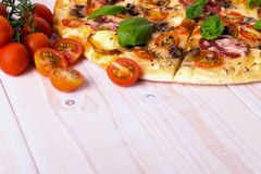 Pizza with Salami Vegetables and Spices on a white wooden background with copy space. Royalty Free Stock Photos