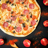 Pizza saporita con gli ingredienti e le spezie su fondo nero Disposizione piana, vista superiore immagine stock