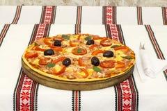 Pizza saporita con le verdure, basilico, olive, pomodori, peperone verde sul tagliere, variopinto tradizionale della tovaglia Fotografie Stock Libere da Diritti