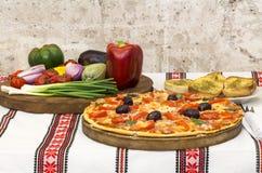 Pizza saporita con le verdure, basilico, olive, pomodori, peperone verde sul tagliere, variopinto tradizionale della tovaglia Fotografie Stock