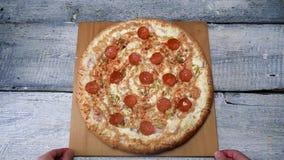 Pizza saporita sul vassoio di legno sul fondo bianco della tavola Pagina I movimenti dell'uomo hanno cotto di recente la pizza co stock footage