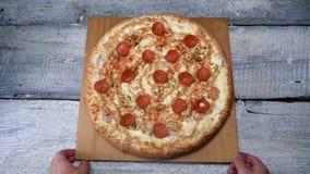 Pizza saporita sul vassoio di legno sul fondo bianco della tavola Pagina I movimenti dell'uomo hanno cotto di recente la pizza co archivi video