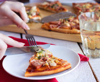 Pizza with sausage, chicken, corn and cheese. Eat pizza hands, Italian cuisine, fork, knife Stock Photography