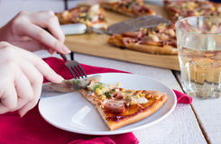 Pizza with sausage, chicken, corn and cheese. Eat pizza hands, Italian cuisine, fork, knife Royalty Free Stock Photo