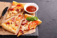 Pizza with sausage, ham, tomato and cheese, decorated with basil and cut into pieces Royalty Free Stock Photo