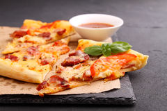 Pizza with sausage, ham, tomato and cheese, decorated with basil and cut into pieces Stock Image