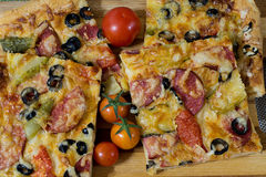 Pizza with sausage, olives, tomatoes and cheese Stock Images