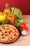 Pizza savoureuse avec des olives et des légumes sur le rouge Photographie stock libre de droits
