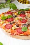Pizza savoureuse avec des tranches de salami sur les conseils blancs Images libres de droits