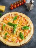 Pizza savoureuse avec le lard, le fromage et la tomate sur le fond foncé Vue de plan rapproché Nourriture délicieuse Photo stock