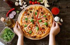 Pizza savoureuse traditionnelle de service sur la table en bois Photographie stock