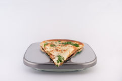 Pizza on Scales. Slice of pizza with cheese and parsley on scales on white background royalty free stock photos