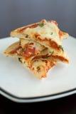 Pizza-Scheiben gestapelt auf einer Platte Stockbild