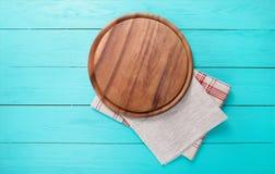 Pizza-Schneidebrett für Lebensmittel und Tischdecke auf blauem hölzernem Hintergrund Draufsicht- und Kopienraum Platz für Text Sp Lizenzfreie Stockbilder
