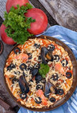 Pizza with seafood and black olives Stock Image